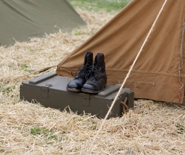 army boots on wooden foot locker outside a tent. - postal worker stok fotoğraflar ve resimler