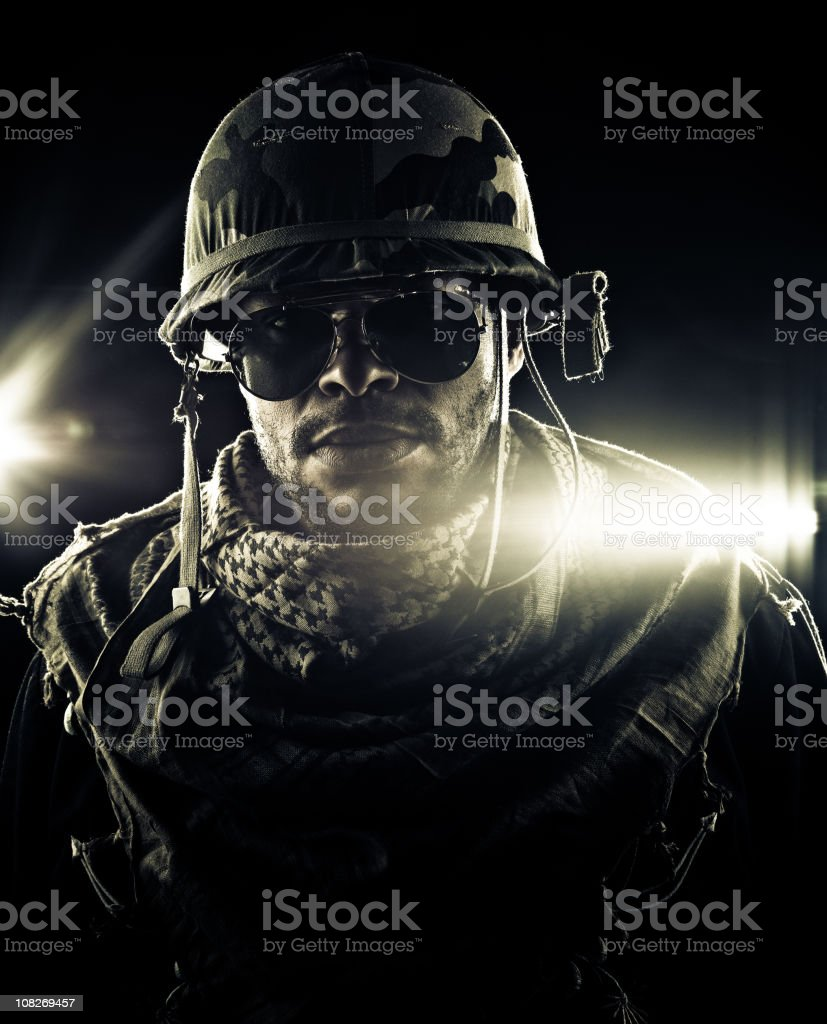 army captain deploying in combat zone Captain Bubba L wearing classic aviator glasses and camo clothes in front of military transports flaring against the camera. Shoot after-HQlypse2009, calgary. thanks member Bubbalove for posing. Adult Stock Photo