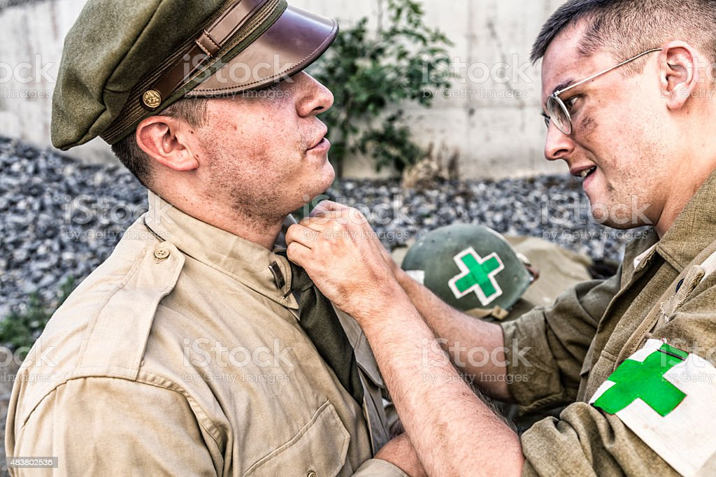 WWII US Army Combat Medic Helping Officer Uniform stock photo