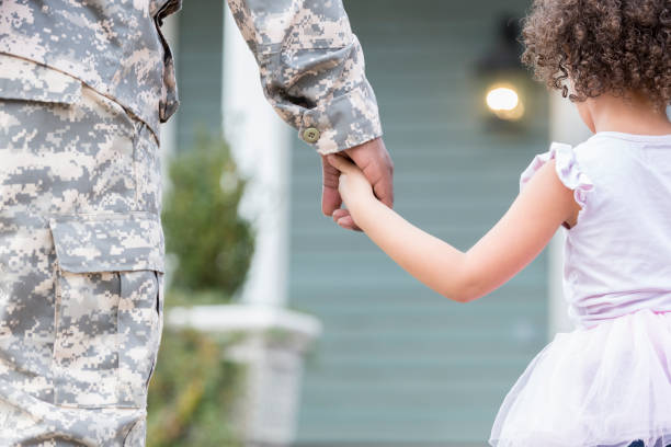 army dad holds hands with young daughter - military lifestyle stock pictures, royalty-free photos & images