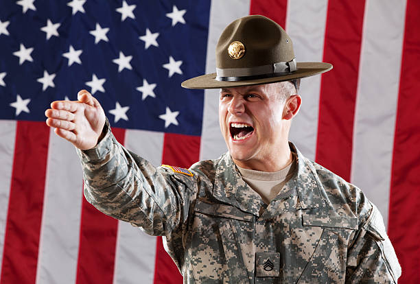U S Army Drill Sergeant Giving Instruction U S Army Drill Sergeant in Army Camouflage Uniform and hat against USA flag. sergeant stock pictures, royalty-free photos & images