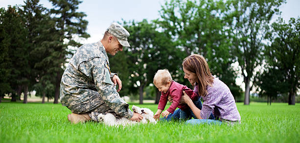 Army Family Series: Real American Soldier With Wife & Son Real American Soldier With Wife & Son playing with their dog in the park.  military lifestyle stock pictures, royalty-free photos & images
