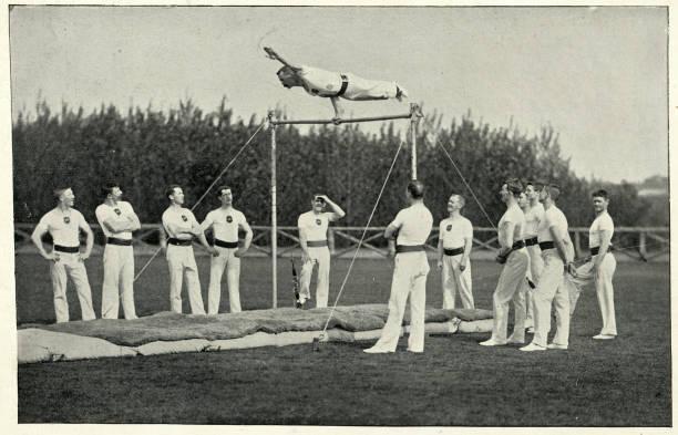 Army gymnast performing the weathercock, gymnastics low bar stock photo