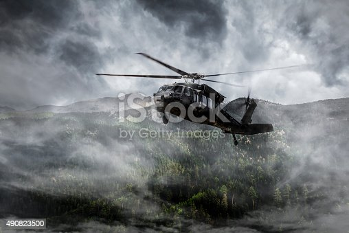 istock Army Helicopter Flies over Foggy Mountains 490823500