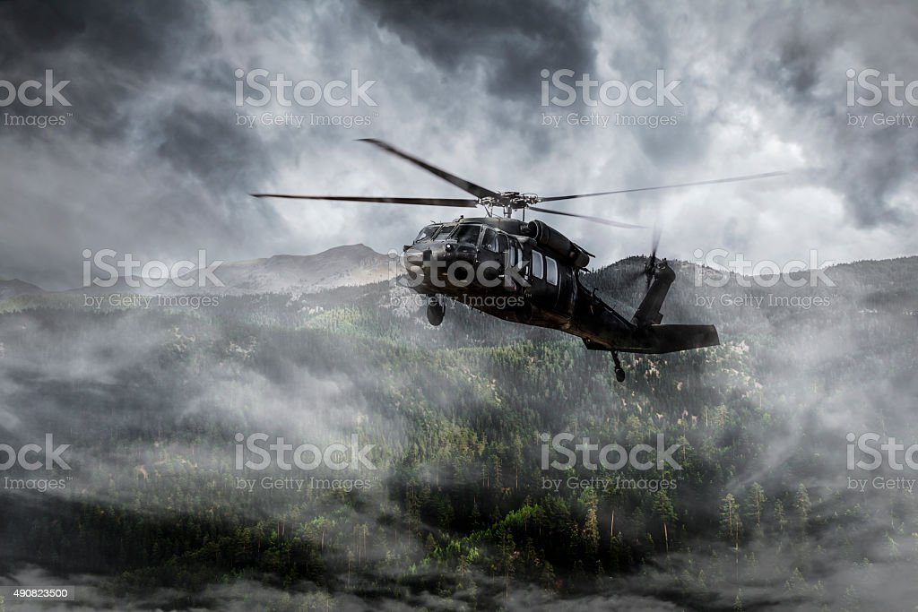Army Helicopter Flies over Foggy Mountains stock photo