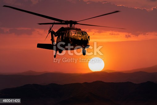 Silhouette aerial view of Army helicopter flying over mountains at sunset.