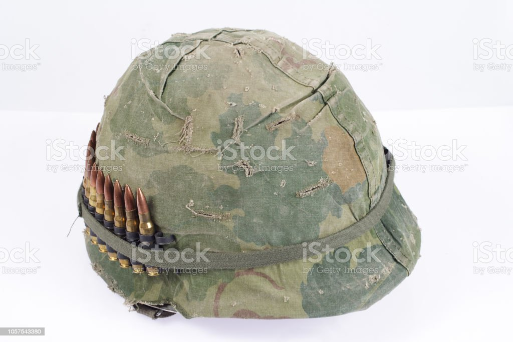 e70d7b31 US Army helmet with camouflage cover and ammo belt - Vietnam war period  royalty-free