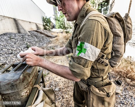 Crop side view portrait of a World War II US Army medic soldier. He is facing camera left as he prepares a medical bandage using water from a jerry can style water container in the back of a Jeep military vehicle. He wears the internationally recognized symbolic white arm band with a red cross symbol to identify him as medical personnel as he tends to wounded personnel. The same red cross symbol is painted on his helmet.  All soldiers/models participating in this photo shoot were/are professional reenactment actors/models, and are dressed in completely authentic, period correct uniforms and helmets They are using only historically correct weapons, equipment, medical gear, vehicles, etc. The only exception to historical accuracy is the red cross symbols on the medic's helmet and white arm band have been altered to a green color rather than red, in deference to the International Red Cross trademark of the