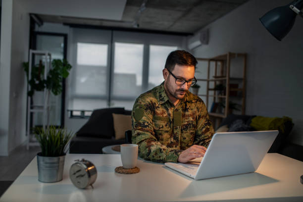 Army man using laptop at home Army man using laptop at home military lifestyle stock pictures, royalty-free photos & images