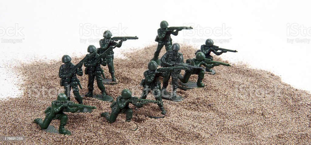 Army Men Charge up Sand in Toy Figurine Still Life stock photo
