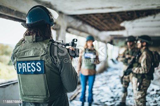 Group of people, war journalist reporting from the war zone, military men giving interview.