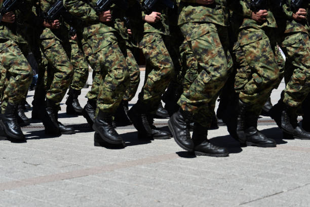 army military soldiers marching in a parade outdoors. - marciare foto e immagini stock