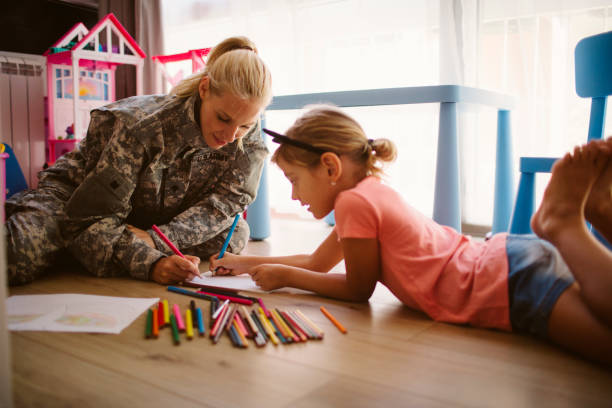 Army Mom Coloring  With Her Little Girl Army Mom Coloring  With Her Little Girl at home. Sitting on the floor and spending time together military lifestyle stock pictures, royalty-free photos & images