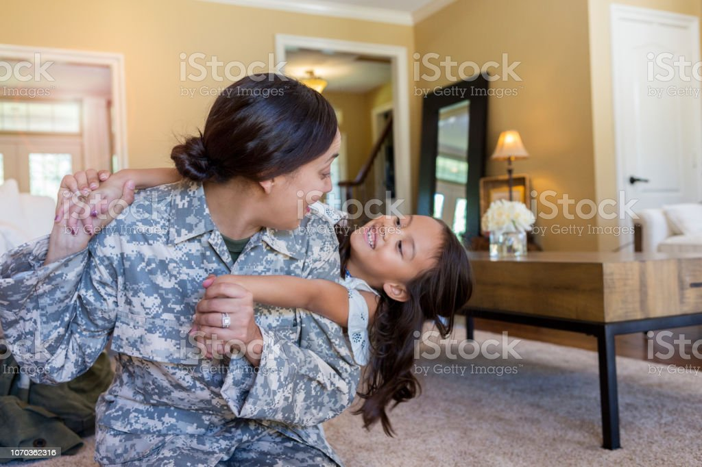 Army mom plays with young daughter stock photo