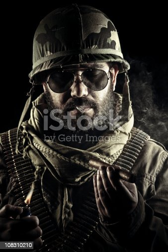 Captain Chang, head and shoulder portrait  wearing military helmet, classic aviator glasses and camo clothes enjoying a victory cigar.