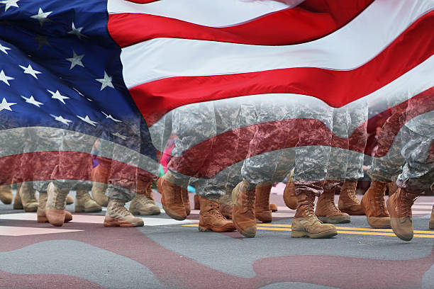 Army Parade & Flag Soldiers dressed in army camouflage in an army parade covered with the flag. us military stock pictures, royalty-free photos & images