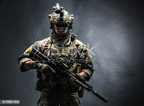 Army soldier in Combat Uniforms with assault rifle, plate carrier and combat helmet are on, Shemagh Kufiya scarf on his neck. Studio shot, dark background