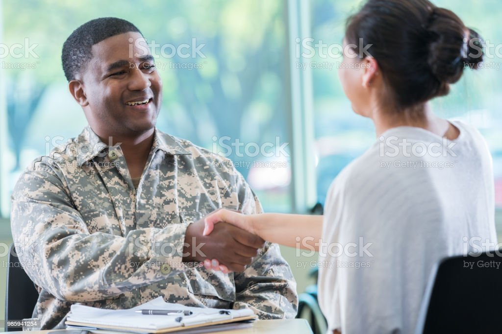 Army recruitment officer greets potential recruit stock photo