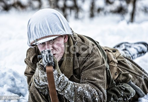 Close-up of a young WWII US Army combat infantry sniper soldier aiming his M1 rifle pointing directly at the camera while lying in an alert, combat-ready prone position outdoors in a winter snow-covered field. A white camouflage cloth covers his standard issue metal helmet and he is wearing a long, high-collared winter overcoat on top of layers of authentic US WWII military standard issue uniform clothing. The soldier is dressed in a complete, completely period-correct uniform with historically accurate weapon, helmet, equipment, supplies, tools, etc. Selective focus on the man's suspicious brown eyes. Professional reenactment actors/models at the January-February 2016 Utah