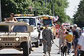 Penfield, New York, USA - July, 4 2008: A United States Army soldier marching with an Army mascot dog next to an Army vehicle at the head of the Penfield town Independence Day parade.