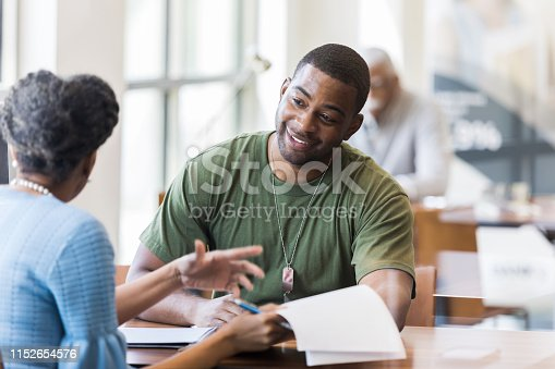A mid adult soldier is happy to hear he qualifies for a good interest rate on his certificate of deposit.