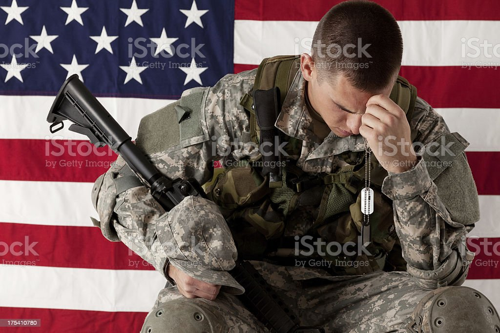 Army soldier sitting in front of American flag Army soldier sitting in front of American flag 20-29 Years Stock Photo