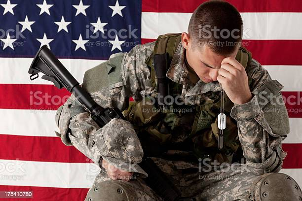 Army Soldier Sitting In Front Of American Flag Stock Photo - Download Image Now