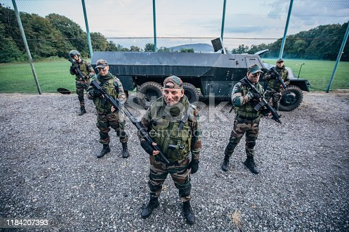 Portrait of a group of army soldiers standing in front of wheeled armored vehicle