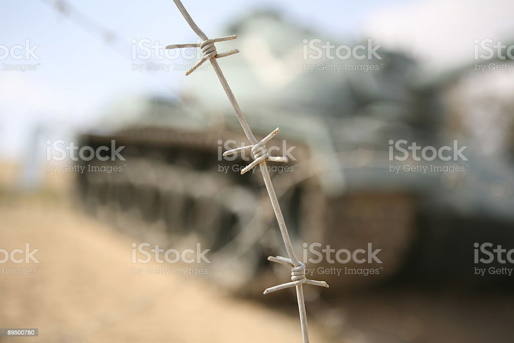 Army tank behind barbed wire royalty-free stock photo