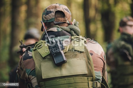 Soldiers in camouflaged clothing with guns, deep in wilderness on a mission, rear view.
