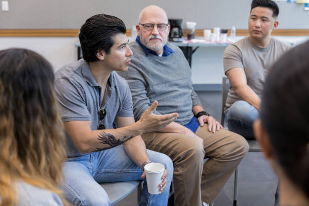 Army veteran has serious conversation during support group meeting Mid adult male army veteran has an intense conversation with an unrecognizable person during a support group meeting. He gestures while speaking. community center stock pictures, royalty-free photos & images