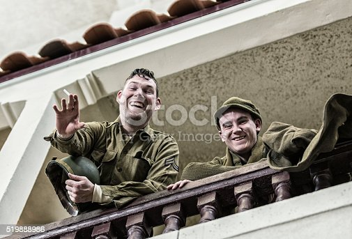 Two World War II US Army soldiers taking a break relaxing, bantering, laughing, waving and flirting with the girls below as they look down from an upstairs balcony at a dance hall.