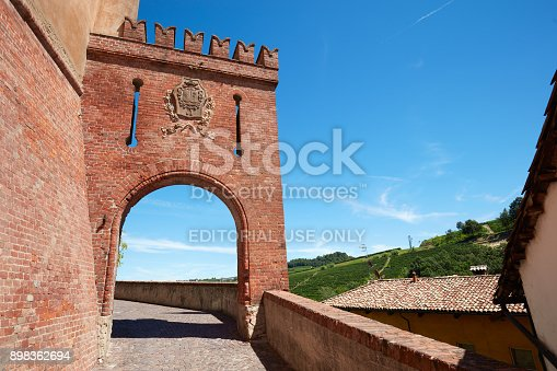 Barolo, Italy - August 6, 2016: Barolo medieval castle entrance arch in red bricks and emblem with empty street in a sunny summer day, blue sky in Barolo, Italy. The Langhe area in Piedmont is Unesco World Heritage Site.