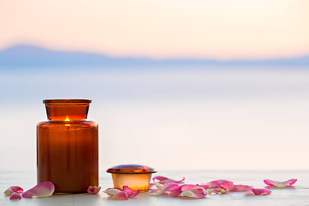 Aroma candle on sunset with rose petals stock photo