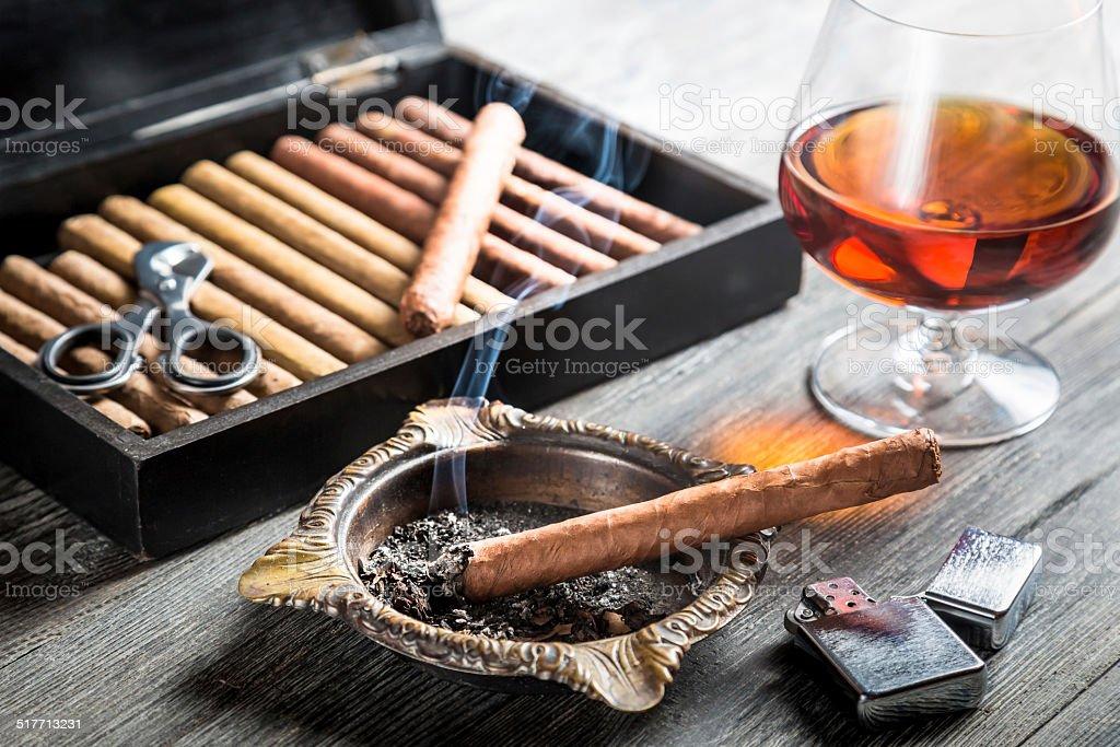 Aroma of cognac and cigar fuming stock photo