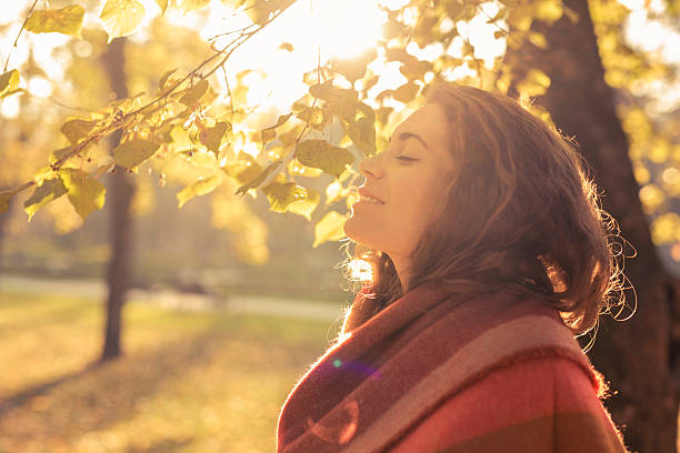 Aroma of the fall Beautiful, young, caucasian woman standing in the park and enjoying with her eyes closed tranquil scene stock pictures, royalty-free photos & images
