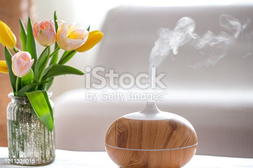 Aroma oil diffuser lamp on the table on a blurred background with a beautiful spring bouquet of tulips.