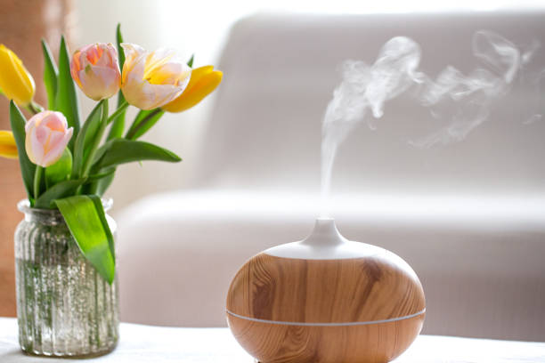 Aroma oil diffuser lamp on the table . Aroma oil diffuser lamp on the table on a blurred background with a beautiful spring bouquet of tulips. aromatherapy stock pictures, royalty-free photos & images