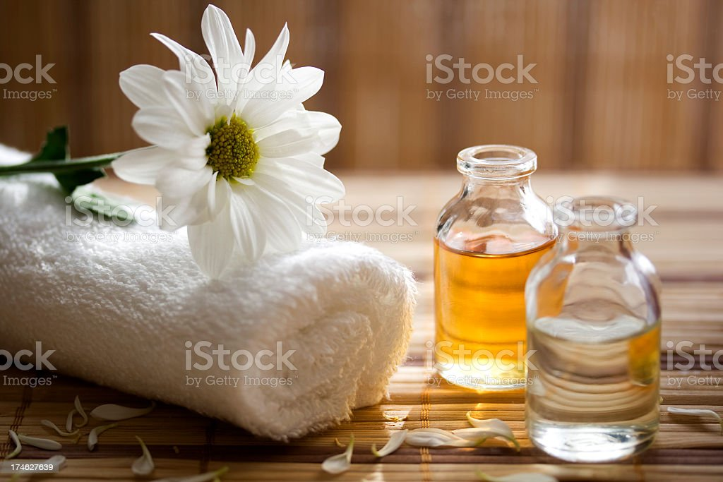 Aroma therapy oils placed next to a white towel and flower stock photo