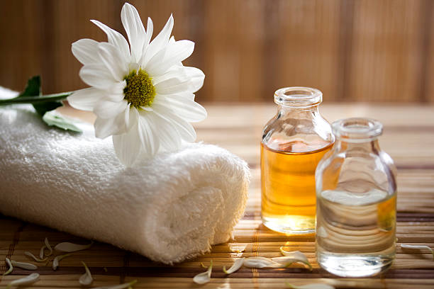 aroma therapy oils placed next to a white towel and flower - aromaterapi stok fotoğraflar ve resimler