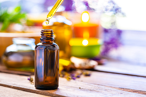 Health care and medicine: close up view of an essential oil bottle with a drop falling from a dropper shot on rustic wooden table. Selective focus on the bottle. The composition is at the left of an horizontal frame leaving useful copy space for text and/or logo at the right. Concepts  for aromatherapy, body care and well being. High resolution 42Mp studio digital capture taken with Sony A7rII and Sony FE 90mm f2.8 macro G OSS lens