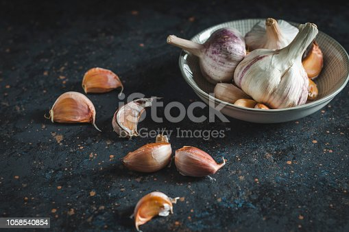 Garlic cloves on rustic table. Garlic in bowl. Fresh peeled garlic and bulbs.