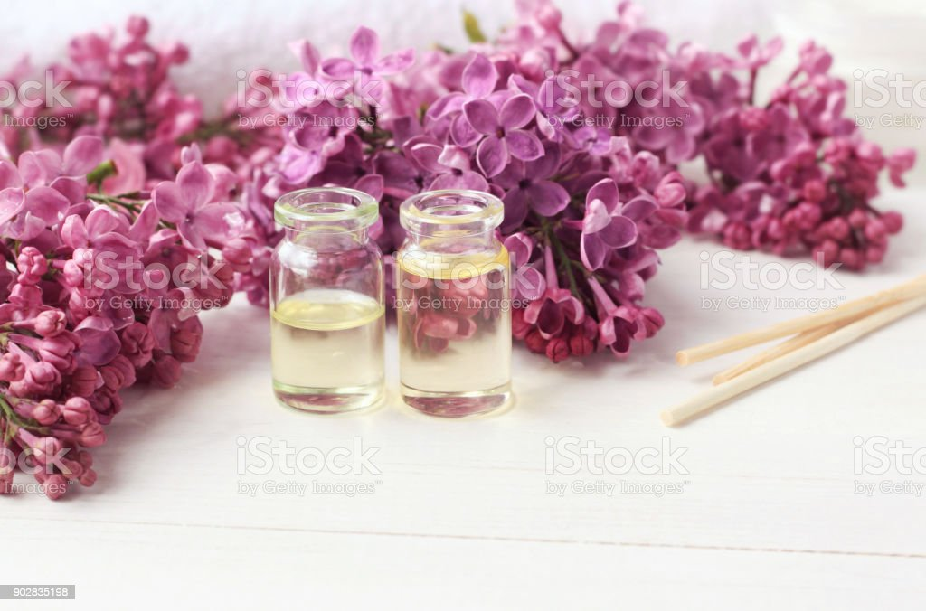 Aromatherapy bottles with floral fragrance, fresh lilac background. stock photo