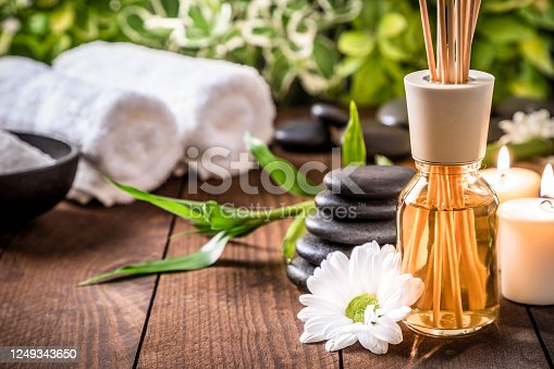 Front view of an aromatherapy diffuser surrounded by a white flower, a stack of hot stones and two burning candles on a wooden table. At the defocused background are two towels and a bowl with salt. Predominant colors are brown and green. Studio shot taken with Canon EOS 6D Mark II and Canon EF 24-105 mm f/4L