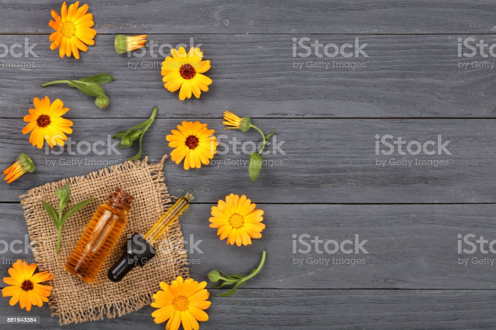 aromatherapy essential oil with marigold flowers on black background with copy space for your text. Top view stock photo