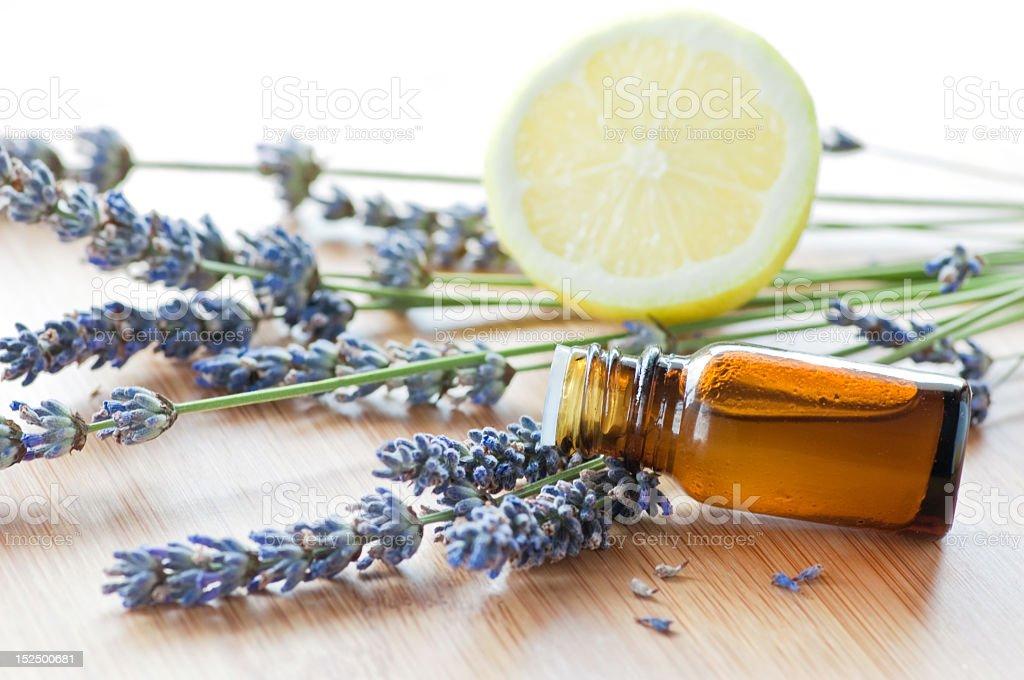 Aromatherapy herbs, oil, and lemon on wood stock photo