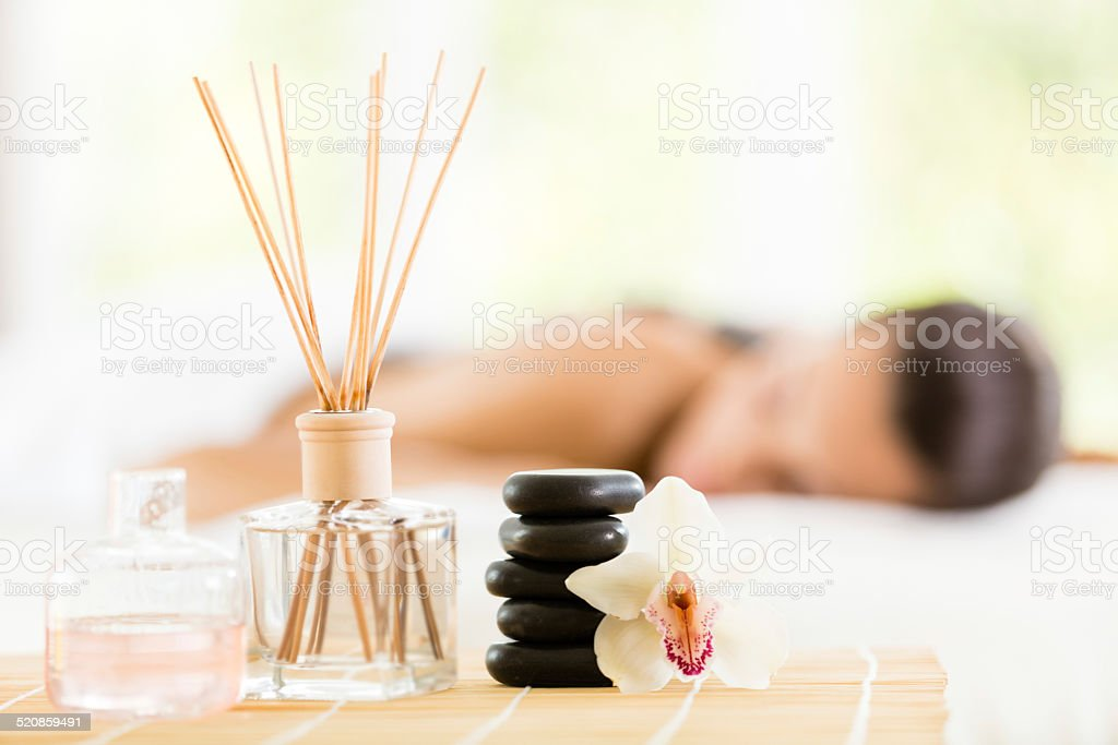 Aromatherapy oils, sticks, flower and massage stones stock photo