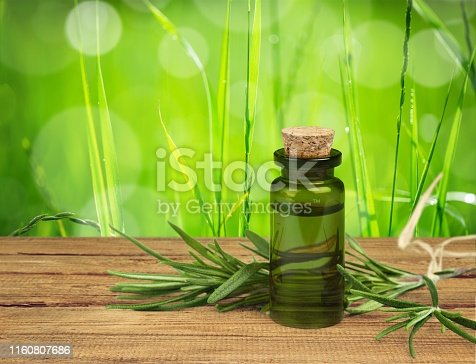Oil bottle and green herbs on blue background
