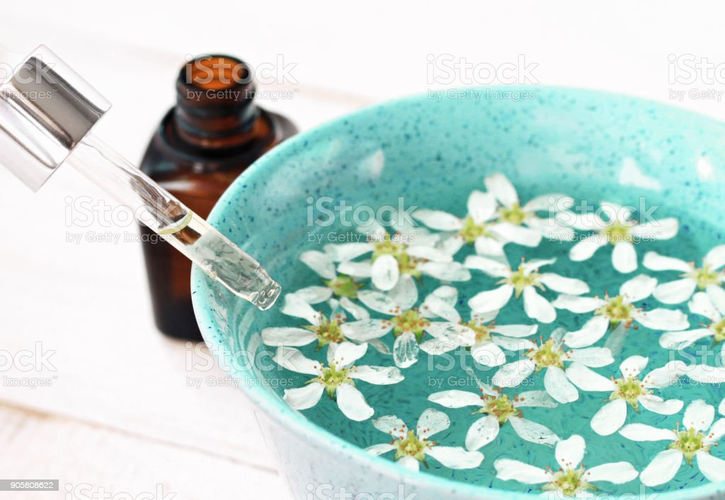 Aromatherapy spa - flowers and essential oils in blue bowl stock photo