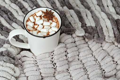 Aromatic cacao drink with marshmallows on cozy soft gray pompon yarn. Holiday concept. Selective focus. Top view.